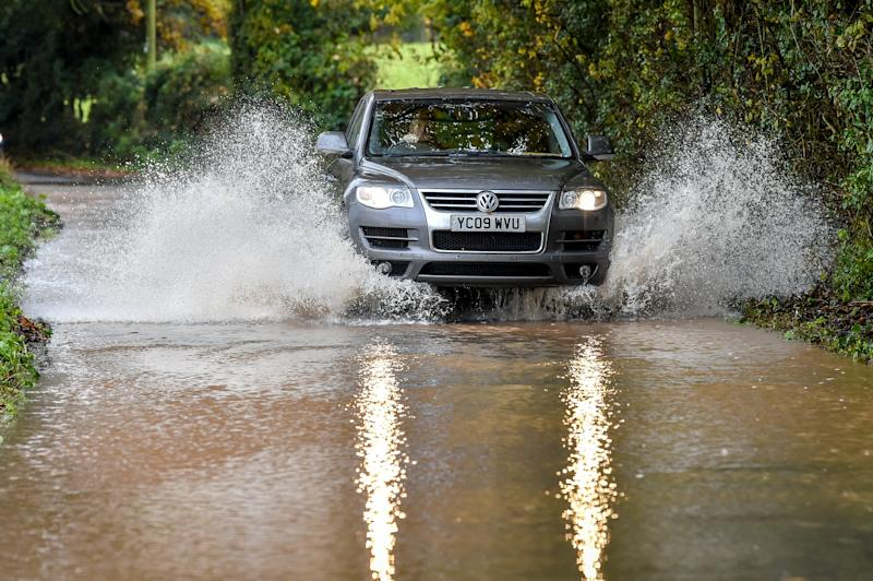 A car drives through floodwater after water has run off fields surrounding Clyst St Mary, Exeter, and flooded the roads after heavy rain. (Photo by Ben Birchall/PA Images via Getty Images)