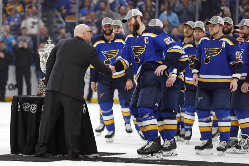 NHL Deputy Commissioner Bill Daly, left, presents the Clarence S. Campbell Bowl to St. Louis Blues' captain Alex Pietrangelo (27) and the rest of the team after the Blues beat the San Jose Sharks after Game 6 of the NHL hockey Stanley Cup Western Conference final series Tuesday, May 21, 2019, in St. Louis. The Blues won 5-1 to win the series 4-2. (AP Photo/Jeff Roberson)