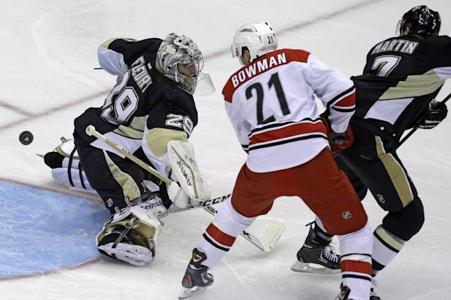 Pittsburgh Penguins goalie Marc-Andre Fleury (29) blocks a shot by Carolina Hurricanes' Drayson Bowman (21) with Penguins' Paul Martin helping on defense during the first period in of an NHL hockey game in Pittsburgh, Tuesday, Oct. 8, 2013. (AP Photo/Gene J. Puskar)
