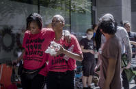 Demetria Hester, second from left,leaves the Multnomah County Justice Center on Monday, Aug. 10, 2020, in Portland, Ore. Hester became a leading activist in the racial justice movement after she was assaulted by a white supremacist three years ago. Authorities said Hester won't be charged following her arrest early Monday. Hester had been booked on suspicion of disorderly conduct and interfering with a police officer during the protest that began Sunday night. Hester's arrest drew a sharp rebuke from national Black Lives Matter activists, who are increasingly focusing on demonstrations in Oregon's largest city. (Brooke Herbert/The Oregonian via AP)