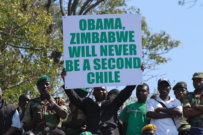 A man holds a poster with a message for United States President Barack Obama at Zimbabwe's Commemoration of Heroes day in Harare, Monday, Aug.12, 2013. Zimbabwean President elect Robert Mugabe was the guest speaker at the event. Mugabe recieved more than 60 percent of the vote in recent Presidential elections while his main challenger Morgan Tsvangirai is challenging the results in court and declaring the election null and void. (AP Photo/Tsvangirayi Mukwazhi)
