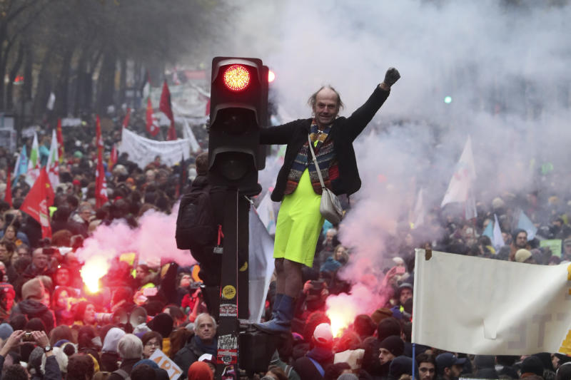 A man stands on a traffic light during a demonstration in Paris, Thursday, Dec. 5, 2019. The Eiffel Tower shut down, France's vaunted high-speed trains stood still and several thousand protesters marched through Paris as unions launched open-ended, nationwide strikes Thursday over the government's plan to overhaul the retirement system. (AP Photo/Thibault Camus)