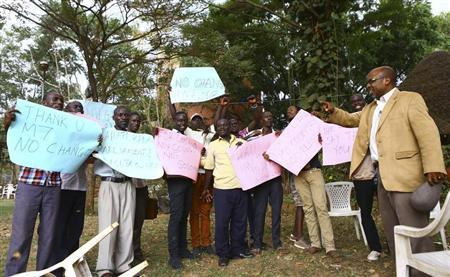 Ugandan anti-gay activist Pastor Ssempa leads anti-gay supporters as they celebrate after Uganda's President Museveni signed a law imposing harsh penalties for homosexuality in Kampala