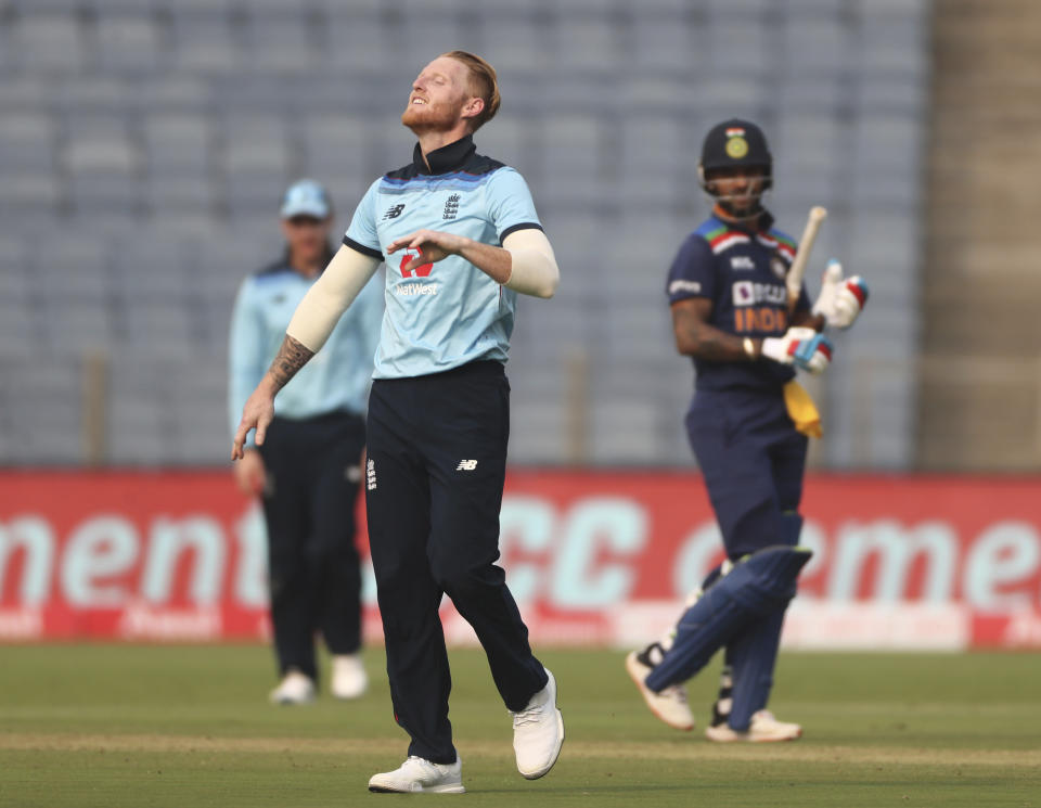 England's Ben Stokes, front, celebrates the dismissal of India's Shikhar Dhawan, right, during the first One Day International cricket match between India and England at Maharashtra Cricket Association Stadium in Pune, India, Tuesday, March 23, 2021. (AP Photo/Rafiq Maqbool)
