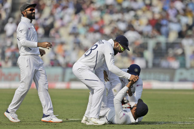 Indian cricket captain Virat Kohli, center, and other teammates congratulate Rohit Sharma, on ground, for taking a catch to dismiss Bangladesh's Mominul Haque during the first day of the second test match in Kolkata, India, Friday, Nov. 22, 2019. (AP Photo/Bikas Das)