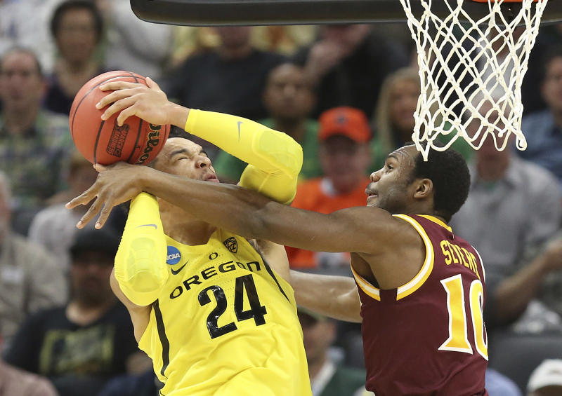 Oregon forward Dillon Brooks, left, goes to the basket against Iona guard Jon Severe, during the first half of a first-round game in the men's NCAA college basketball tournament in Sacramento, Calif., Friday, March 17, 2017. (AP Photo/Steve Yeater)