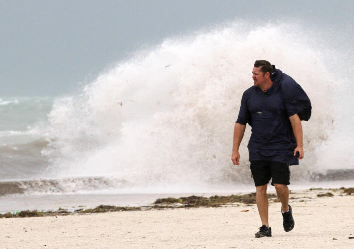 A man walks on the beach in Key West, Fla., Sunday, Aug. 26, 2012 as heavy winds hit the northern coast from Tropical Storm Isaac. Isaac is expected to continue streaming across Marion County Monday as it continues toward the northern Gulf of Mexico. National Weather Service officials in Jacksonville on Sunday said Marion County began getting rain bands from Isaac around 2 p.m. and that the rain would continue through Tuesday. (AP Photo/Alan Diaz)