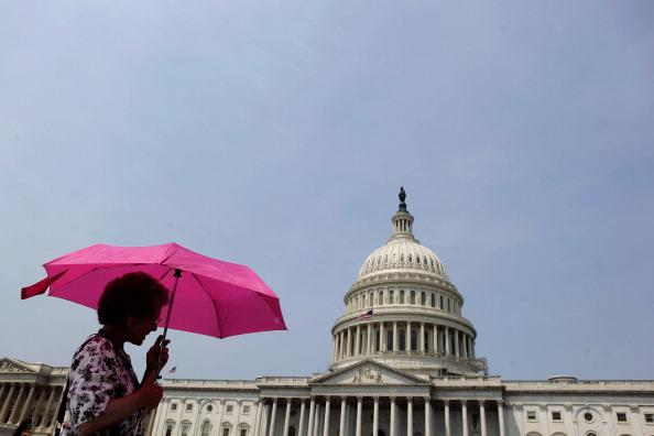 As temperatures top 100-degrees in the nation's capital, visitors take their shade with them by carrying umbrellas as they tour the U.S. Capitol grounds June 29, 2012 in Washington, DC. Heat warnings are up and people are being told to stay indoors as the heat index will soar to around 110-degrees Friday and Saturday. (Photo by Chip Somodevilla/Getty Images)