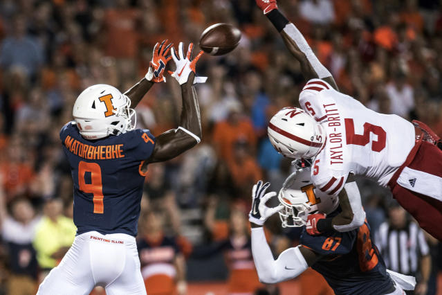 Illinois' Josh Imatorbhebhe (9) attempts a catch in the end zone as Nebraska's Cam Taylor-Britt (5) defends in the first half of an NCAA college football game, Saturday, Sept. 21, 2019, in Champaign, Ill. Also shown is Illinois' Daniel Barker (87). (AP Photo/Holly Hart)