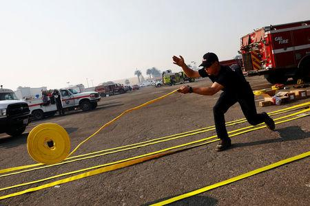 A Cal Fire firefighter unrolls new hoses before they are packed to fight wildfire at the Ventura County Fairgrounds fire camp during the Thomas fire in Ventura, California, U.S. December 12, 2017. REUTERS/Patrick T Fallon