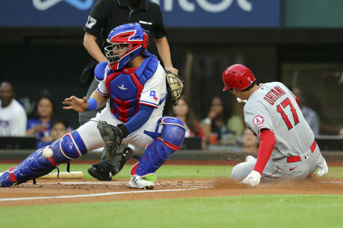 Texas Rangers catcher Jose Trevino, left, gets the ball late as Los Angeles Angels starting pitcher Shohei Ohtani, right, scores in the first inning during a baseball game on Monday, April 26, 2021, in Arlington, Texas. (AP Photo/Richard W. Rodriguez)
