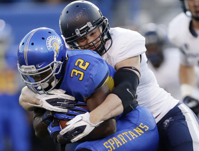 San Jose State running back Jason Simpson (32) is tackled by Utah State linebacker Zach Vigil during the first half of an NCAA college football game Friday, Sept. 27, 2013, in San Jose, Calif. (AP Photo/Marcio Jose Sanchez)