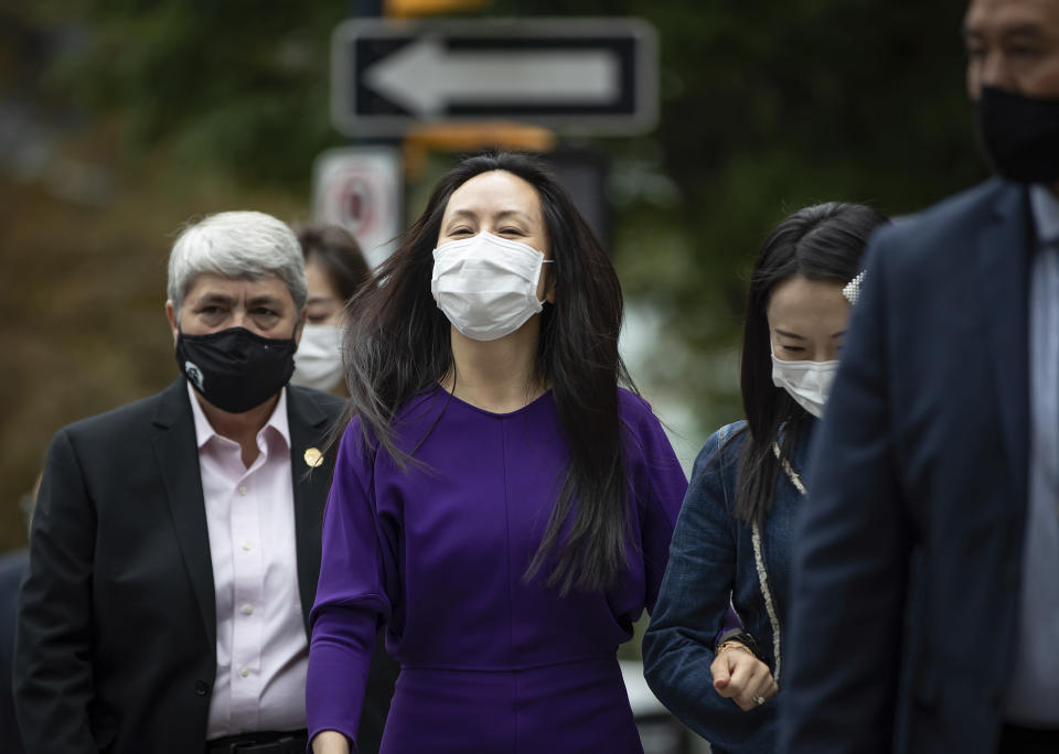 Meng Wanzhou, center, chief financial officer of Huawei, leaves B.C. Supreme Court during a break from her extradition hearing, Wednesday, Aug. 18, 2021, in Vancouver, British Columbia. (Darryl Dyck/The Canadian Press via AP)