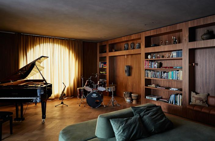 """<div class=""""caption""""> The walls and floor of the music room are lined in walnut and oak. The ceiling is dark stucco, creating an intimate and acoustically ideal room. As all the kids love to play instruments, this is the room where most of the action occurs on the weekends. </div>"""