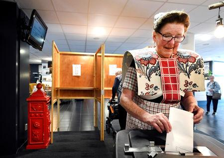 FILE PHOTO: A woman dressed in a traditional costume casts her vote in European Parliament election in Bunschoten-Spakenburg, the Netherlands May 23, 2019. REUTERS/Piroschka van de Wouw/File Photo