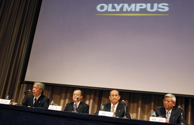 FILE - In this Feb. 27, 2012 file photo, newly-appointed President of Olympus Corp. Hiroyuki Sasa, left, speaks as his predecessor Shuichi Takayama, second left, and two outside directors of the company, Hiroshi Kuruma, second right, and Yasuo Hayashida, attend a press conference in Tokyo when the entire board of scandal-tainted Olympus resigned and the new president was tapped to lead a turnaround at the Japanese medical equipment maker. Sony and Olympus have agreed on a business alliance that will see Sony Corp. invest 50 billion yen ($640 million) for an 11 percent stake in the embattled medical equipment and camera company. Olympus has been on shaky ground after its British chief executive turned whistleblower and helped unearth a scandal involving a systematic cover-up of massive losses. (AP Photo/Koji Sasahara)