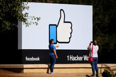 FILE PHOTO: Two women take photos in front of the entrance sign to Facebook headquarters in Menlo Park