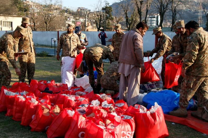 Pakistan Army soldiers pack relief goods to distribute among people in affected areas after heavy snowfall and avalanches, in Muzaffarabad,