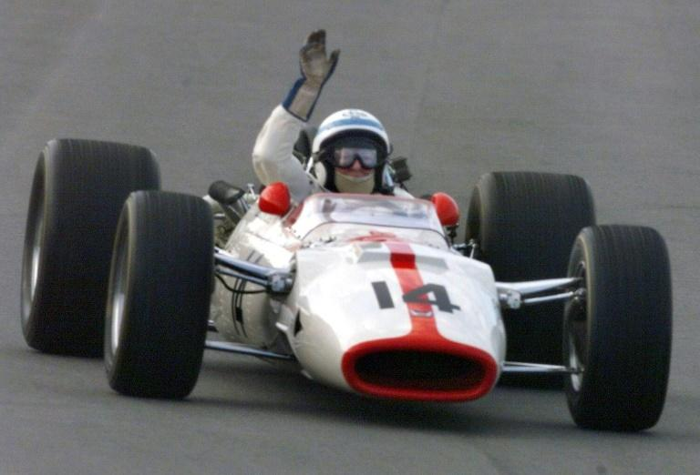 John Surtees waves on a 1967 Honda Formula One car during Honda's 50th anniversary event in Tochigi Prefecture, some 150 kilometers north of Tokyo in October 1998