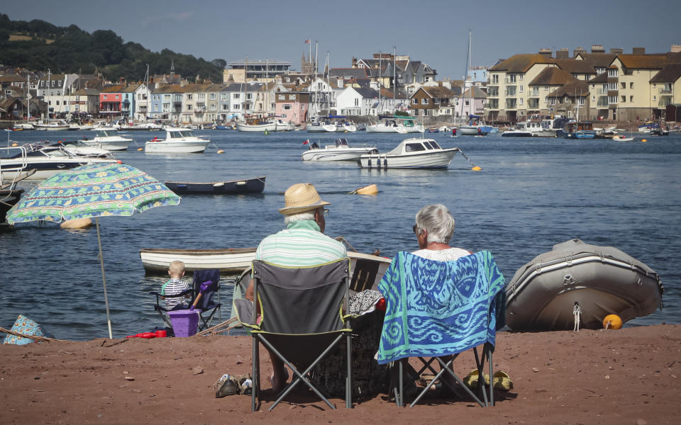 People sit on the beach facing the Teign estuary and the the holiday resort of Teignmouth in Shaldon, Devon, England, Wednesday July 21, 2021. Visiting the fishing village of Shaldon a small cluster of mainly Georgian houses and shops at the mouth of the River Teign, is like stepping back into a bygone era. It features simple pleasures that hark back to analog, unplugged summer days: a book and a picnic blanket, a bucket and spade, fish and chips. These are the traditional trappings of the great British seaside holiday that is making a comeback amid foreign travel concerns during the COVID-19 pandemic. (AP Photo/Tony Hicks)