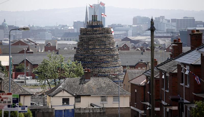 A massive bonfire dwarfs the houses in close to Lanark Way in West Belfast, Northern Ireland, Wednesday, July 10, 2013. Hundreds of fires will be set alight at midnight, on July 11, as Protestant loyalist's celebrate July 12, to mark the defeat of the Catholic King James, by the Protestant William of Orange in 1690. (AP Photo/Peter Morrison)