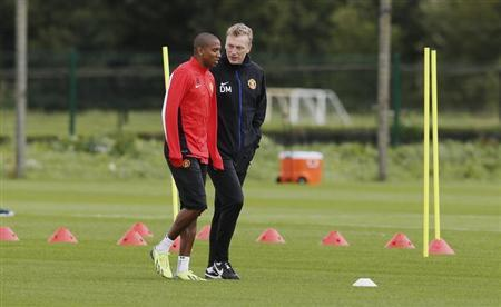 Manchester United's manager Moyes talks with Young during a training session in Manchester