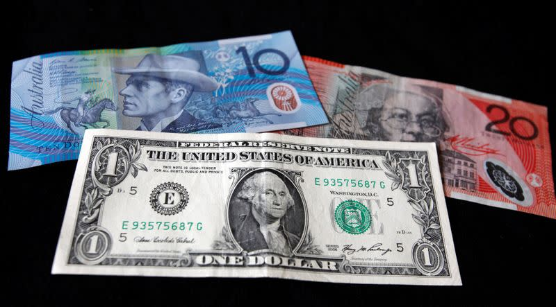 FILE PHOTO: A US dollar note is pictured alongside Australian dollars in this picture illustration taken in Washington