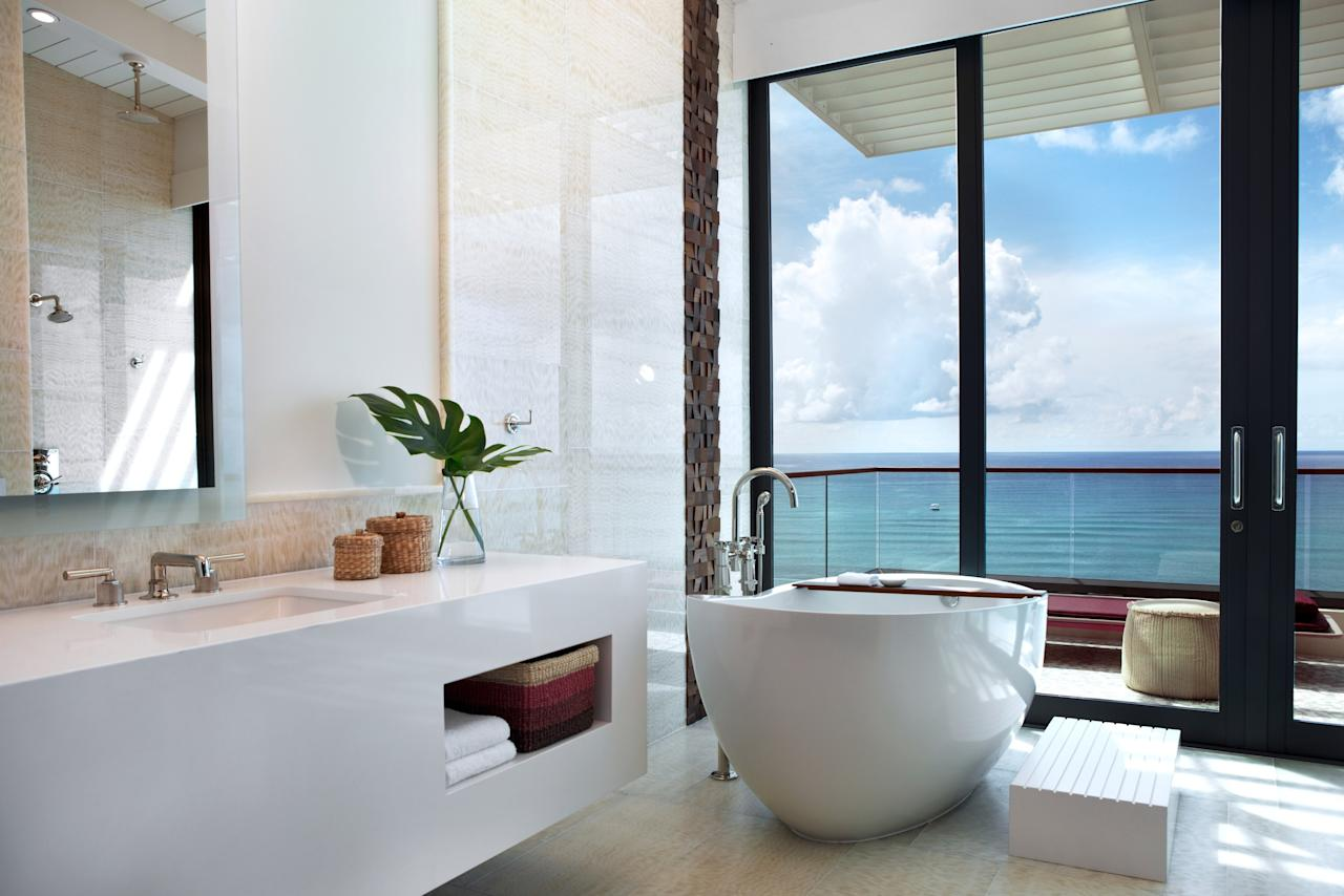 "The 4,700-square-foot Presidential Suite at the Kimpton Seafire Resort + Spa offers sweeping views of the award-winning Seven Mile Beach (the stretch of sand was recently named ""The Caribbean's Best Beach"" in <em>Caribbean Travel and Life</em> magazine). The designers Dayna Lee and Ted Berner made certain that guests could see the Caribbean Sea from every room, including the master bathroom, which featues a white onyx floating tub to relax in while watching the sunset. <a rel=""nofollow"" href=""https://www.seafireresortandspa.com/"">seafireresortandspa.com</a>"