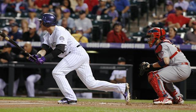 Colorado Rockies' Troy Tulowitzki, left, follows the flight of his two-run single in front of St. Louis Cardinals catcher Yadier Molina in the first inning of a baseball game in Denver on Wednesday, Sept. 18, 2013. (AP Photo/David Zalubowski)