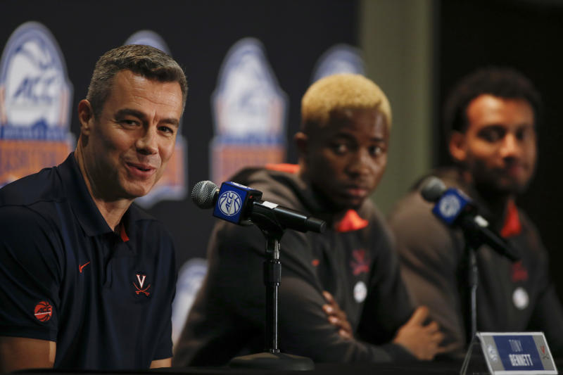 Virginia coach Tony Bennett, left, answers a question as players Mamadi Diakite, center, and Braxton Key look on during the Atlantic Coast Conference NCAA college basketball media day in Charlotte, N.C., Tuesday, Oct. 8, 2019. (AP Photo/Nell Redmond)
