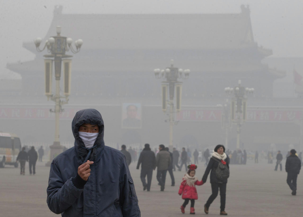 <p>               A man wears a mask on Tiananmen Square in thick haze in Beijing Tuesday, Jan. 29, 2013. Extremely high pollution levels shrouded eastern China for the second time in about two weeks Tuesday, forcing airlines in Beijing and elsewhere to cancel flights because of poor visibility and prompting government warnings for residents to stay indoors. (AP Photo/Ng Han Guan)
