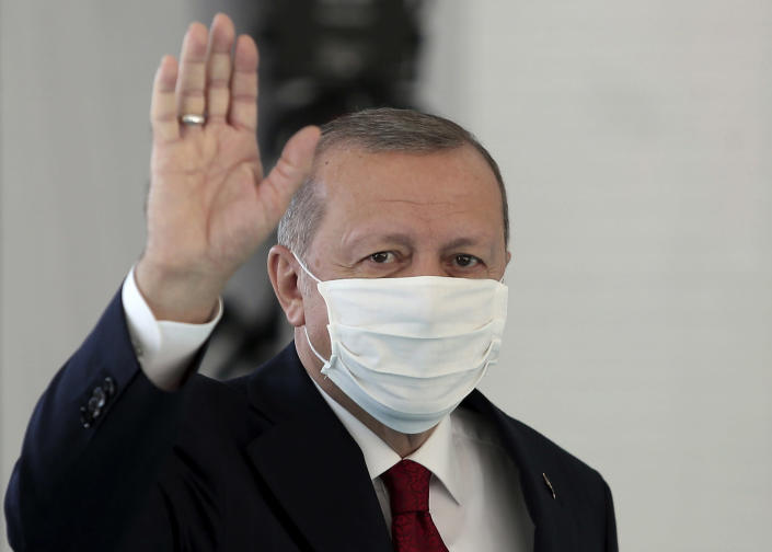 FILE - In this Friday, May 29, 2020, file photo, Turkey's President Recep Tayyip Erdogan, wearing a mask for protection against the coronavirus, arrives to inaugurate a new hospital in Istanbul. When Turkey changed the way it reports daily COVID-19 infections, it confirmed what medical groups and opposition parties have long suspected — that the country is faced with an alarming surge of cases that is fast exhausting the Turkish health system. The official daily COVID-19 deaths have also steadily risen to record numbers in a reversal of fortune for the country that had been praised for managing to keep fatalities low. With the new data, the country jumped from being one of the least-affected countries in Europe to one of the worst-hit.(Can Erok/DHA via AP, File)