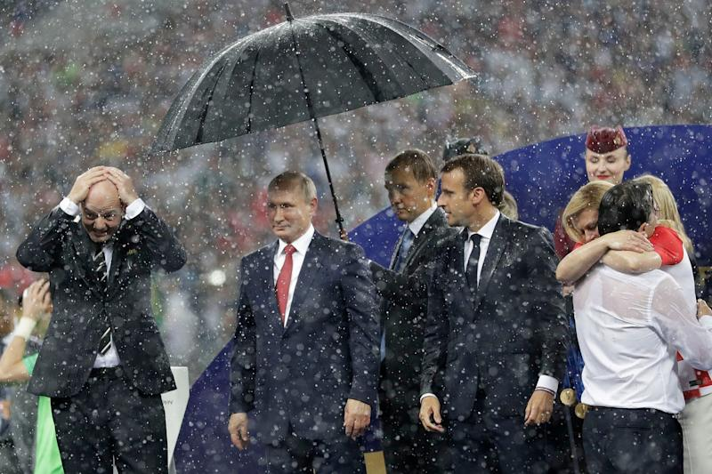 Russian President Vladimir Putin stands under an umbrella while those around him get soaked: AP