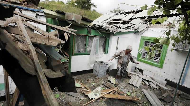 A man walks through the yard of his home, destroyed from shelling between Ukrainian Forces and pro-Russian separatists in Berdyianske village, in the Donetsk region on July 1, 2015 (AFP Photo/Anatolii Stepanov)