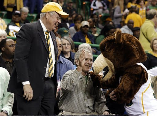 Baylor President Ken Starr, left, smiles as former President George W. Bush jokes around with the university's mascot before a second-round game against Florida State in the women's NCAA college basketball tournament, Tuesday, March 26, 2013, in Waco, Texas. (AP Photo/Tony Gutierrez)