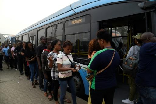 Passengers queue to board a bus provided by the government to offset the impact of the okada and keke ban. Passengers say fares have increased