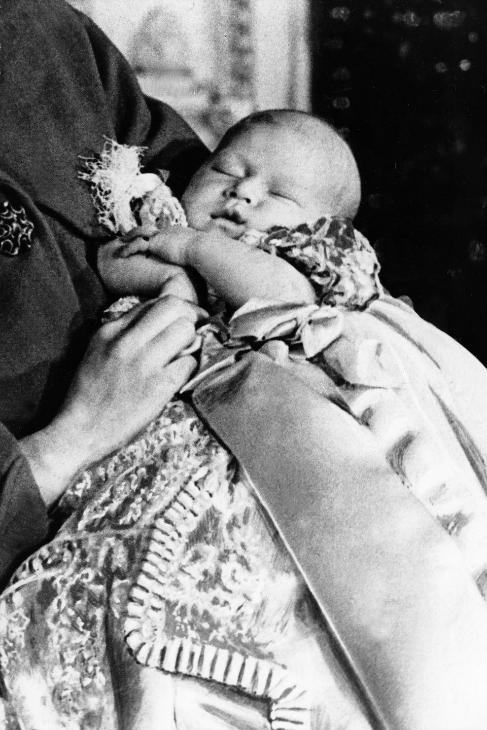 <p> A sleeping Charles is held by his mom, Queen Elizabeth II, at just one month old. The Prince was born on November 14, 1948, at Buckingham Palace.</p>