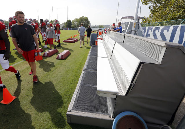 Tampa Bay Buccaneers players stand next to a cooling bench as they take part in a combined NFL football training camp with the Tennessee Titans on Wednesday, Aug. 15, 2018, in Nashville, Tenn. The Titans put a bench on each side of their three practice fields, giving players a chance to recover when the temperature during morning practices can feel like 90 degrees. (AP Photo/Mark Humphrey)
