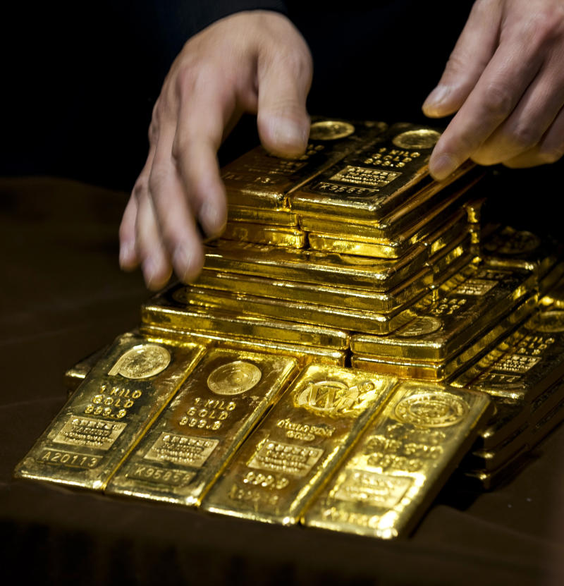 A staff member displays gold bullion bars during a news conference at the Chinese Gold and Silver Exchange Society in Hong Kong Monday, Oct. 17, 2011. The Chinese Gold and Silver Exchange Society started gold trading in yuan on Monday in Hong Kong. (AP Photo)