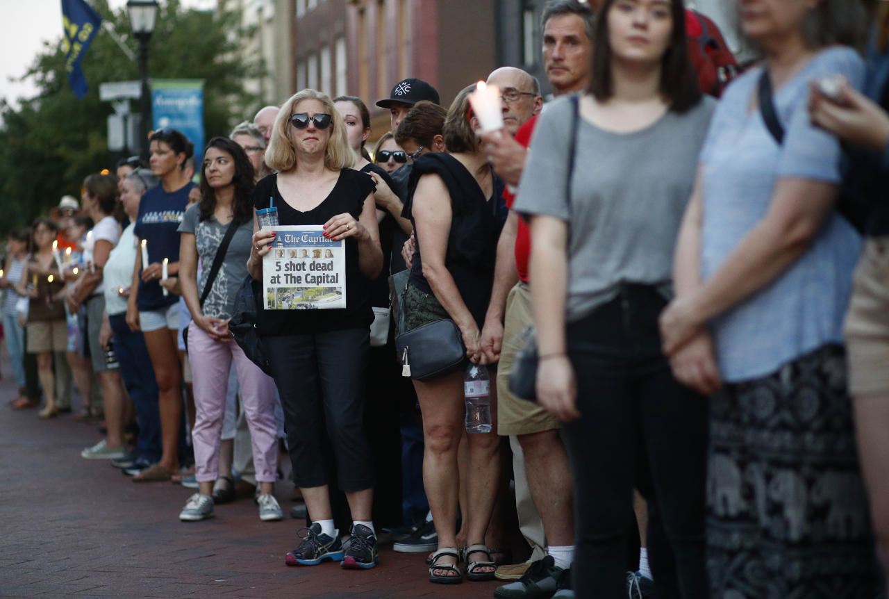 <p>People stand in silence during a vigil in response to a shooting in the Capital Gazette newsroom Friday, June 29, 2018, in Annapolis, Md. Prosecutors say Jarrod W. Ramos opened fire Thursday in the newsroom. (Photo: Patrick Semansky/AP) </p>