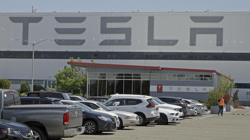 FILE - In this May 11, 2020, file photo, a man walks in the Tesla plant parking lot in Fremont, Calif. Tesla says it delivered more electric vehicles worldwide in the second quarter than it did in the first. The increase came even though coronavirus restrictions forced it to shut down its only U.S. factory for much of the period. (AP Photo/Ben Margot, File)