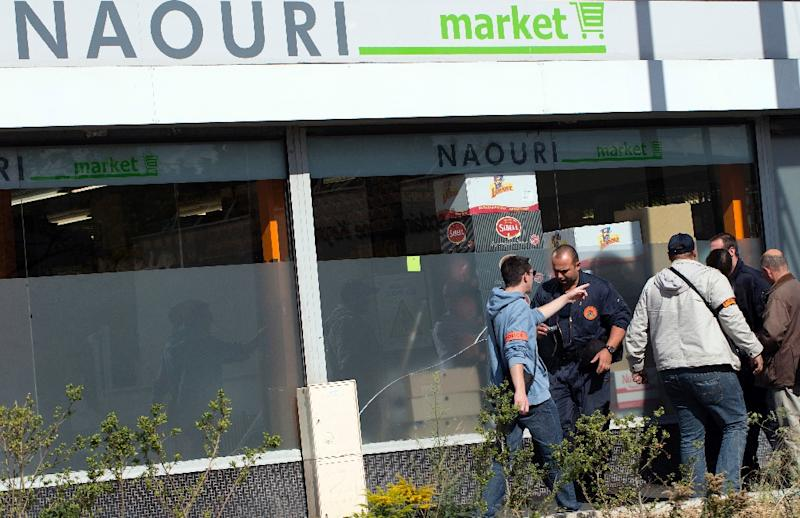 French policemen investigate the site of a bomb explosion in a kosher supermarket in Sarcelles, northern suburb of Paris, on September 19, 2012