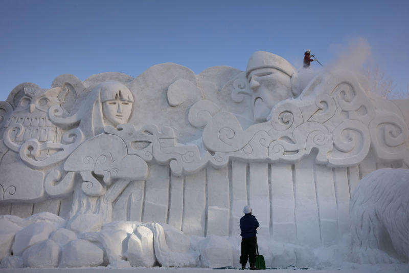 "Two workers remove fresh snow piled on a large snow sculpture at the annual Sapporo Snow Festival, Feb. 4, 2020, in Sapporo, Hokkaido, Japan. After two months of almost no snow, Japan's northern city of Sapporo was overwhelmed with the white stuff. The snowfall was good news for tourism, for the ""look""of the annual Sapporo Snow Festival, and for organizers who hope to bring the 2030 Winter Olympics to the city. Sapporo hosted the Winter Olympics back in 1972. (AP Photo/Jae C. Hong)"