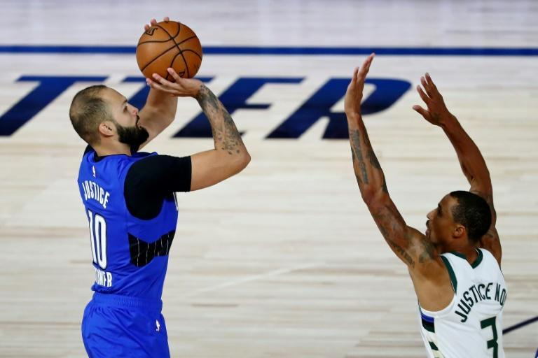 Evan Fournier prend un tir malgré la défense de George Hill de Milwaukee, lors du succès du Magic en playoffs NBA dans la bulle de Disney, le 18 août2020