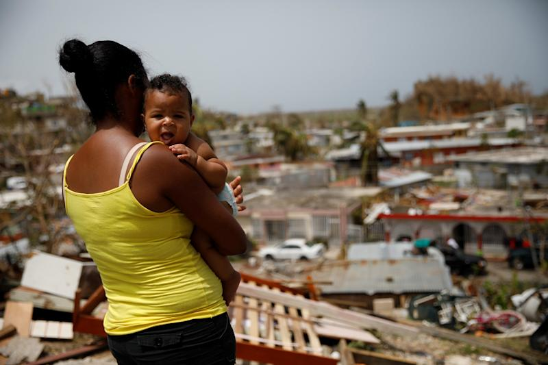 A woman carrying her baby looks at the damage in Canovanason Sept. 26. (Carlos Garcia Rawlins/Reuters)