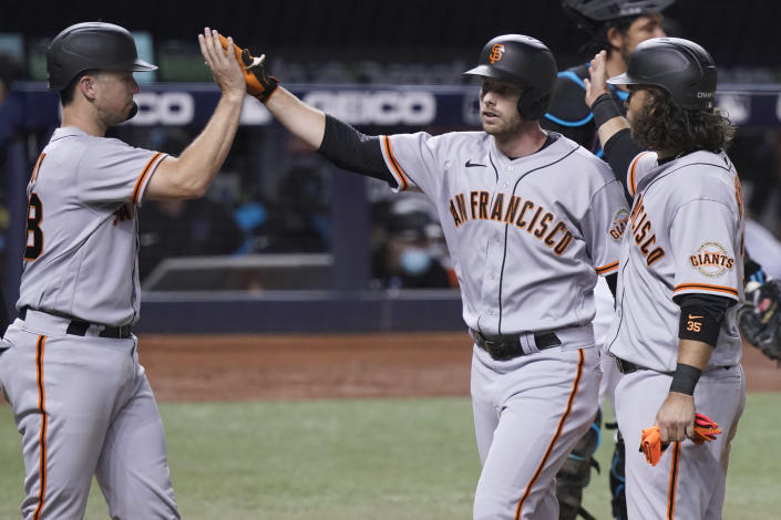 San Francisco Giants' Austin Slater, center, is congratulated by Buster Posey, left, and Brandon Crawford after Slater hit a three-run home run during the seventh inning of the team's baseball game against the Miami Marlins, Saturday, April 17, 2021, in Miami. (AP Photo/Marta Lavandier)