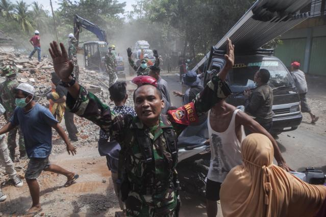 <p>A soldier calmed the panic residents during an powerful earthquake of 6.2 scala righter in Lombok, Indonesia, on Aug. 09, 2018. (Photo: Agoes Rudianto/Barcroft Media via Getty Images) </p>