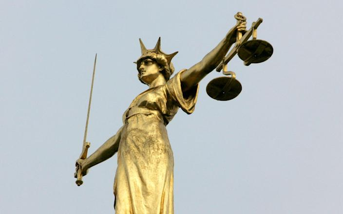A statue representing the scales of justice - TOBY MELVILLE