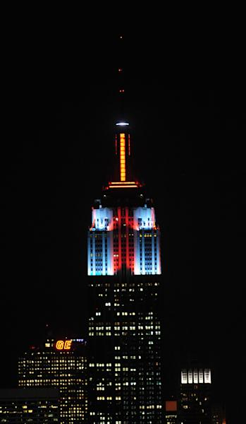 In this Nov. 26, 2012, photo provided by the Empire State Building, the top floors of New York's Empire State Building are lit in gold, red, blue and white light after they being switched on by R&B star Alicia Keys. The landmark boasts a new LED lighting system with a palette of more than 16 million colors in limitless combinations, including ripples, sparkles, chasers, sweeps, strobes and bursts. The old lights came in only 10 colors. (AP Photo/Empire State Building, Bryan Smith)
