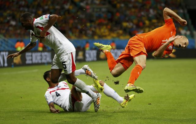 Arjen Robben of the Netherlands (R) falls after a challenge by Costa Rica's Celso Borges (5) and Michael Umana during their 2014 World Cup quarter-finals at the Fonte Nova arena in Salvador July 5, 2014. REUTERS/Sergio Moraes (BRAZIL - Tags: SOCCER SPORT WORLD CUP TPX IMAGES OF THE DAY)